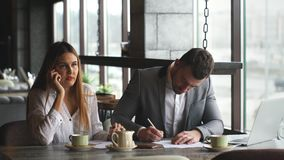 Businesswoman talking on the phone, the businessman signs documents and typing on a laptop. Two Young Businesspeople Working On Laptop In Coffee Shop stock footage