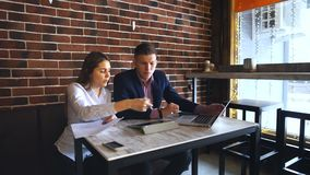 Two Young Businesspeople Working On Laptop In Coffee Shop. Happy business people working together on laptop and sign documents stock video
