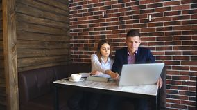 Two Young Businesspeople Working On Laptop In Coffee Shop. Happy business people working together on laptop and sign documents stock video footage