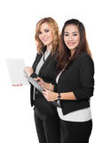 Two young businesswoman discuss with a clipboard, isolated Royalty Free Stock Photos