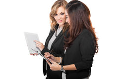 Two young businesswoman discuss with a clipboard, isolated Stock Image