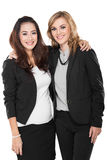 Two young businesswoman in a friendly hug, isolated royalty free stock image