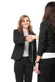 Two young businesswoman making a deal and shaking hands isolated Royalty Free Stock Photos