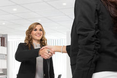Two young businesswoman making a deal and shaking hands Royalty Free Stock Photography