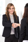 Two young businesswoman making a deal and shaking hands Stock Photo