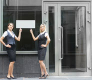 Two young businesswoman pointing at a banner Royalty Free Stock Photos
