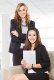 Two young businesswoman sitting and standing next to each other, Stock Photo
