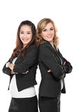 Two young businesswoman smiling while leaning againts each other Royalty Free Stock Photography