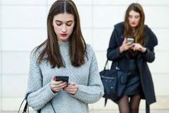 Two young businesswoman using mobile phone in the street. Royalty Free Stock Photos