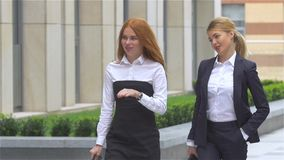 Two young businesswoman walking on the street near office building, slow motion stock video