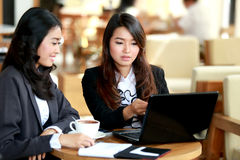 Two young businesswoman working at cafe Stock Photos
