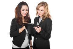 Two young businesswoman wtih a clipboard, isolated Stock Photo