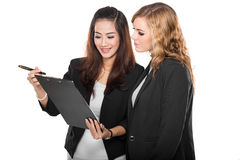 Two young businesswoman wtih a clipboard, isolated. A portrait of a two young businesswoman wtih a clipboard, isolated Stock Images
