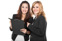 Two young businesswoman wtih a clipboard, isolated Royalty Free Stock Image