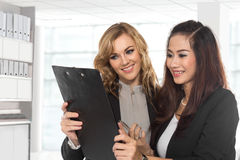 Two young businesswoman wtih a clipboard Stock Images