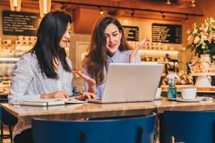 Two young businesswomen, bloggers, wearing in shirts are sitting in cafe at table and using laptop, working Stock Photo