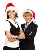 Two young businesswomen in Christmas hats Royalty Free Stock Images