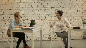 Two young businesswomen having a meeting in the office sitting. At a desk having a discussion with focus to a young woman wearing glasses stock video