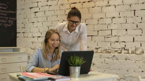 Two young businesswomen having a meeting in the office sitting. At a desk having a discussion with focus to a young woman wearing glasses stock footage