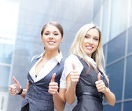 Two young businesswomen holding thumbs up Stock Image