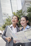 Two young businesswomen with the map looking for location Royalty Free Stock Photo