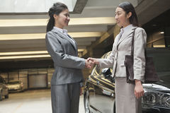 Two young businesswomen shaking hands in parking garage Stock Photos