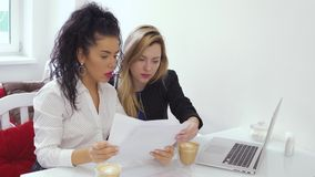 Two young caucasian women discusses working issues in cafe. Two young businesswomen sits at the table in cafe and working with laptop. Brunette shows some stock video