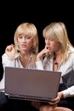 Two young businesswomen sitting with laptop Royalty Free Stock Photo