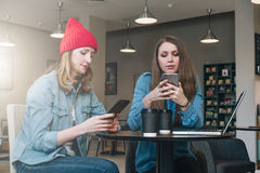 Two young businesswomen sitting at table in coffe shop, look at your smartphone screen and discuss business strategy Stock Photography