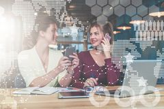 Two young businesswomen are sitting at table.First girl is holding smartphone,second is talking on cell phone Stock Photos