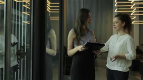 Two young businesswomen talking in lobby in office center. Two young businesswomen standing in the lobby of business center. Two colleagues talking and smiling stock video footage