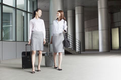 Two young businesswomen walking with suitcases and talking Royalty Free Stock Image