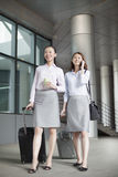 Two young businesswomen walking with suitcases and talking Royalty Free Stock Photography