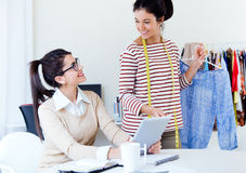 Two young businesswomen working with digital tablet in her offic Royalty Free Stock Photo