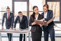 Two young businesswomen working together with folder while businessmen standing behind. Business team working concept Royalty Free Stock Photography
