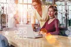 Two young businesswomen working together on laptop in office. In foreground are virtual graphs, charts, data, diagrams. Royalty Free Stock Image