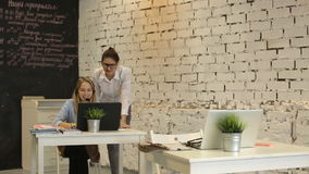 Two young businesswomen works at the computer. Two young businesswomen having a meeting in the office sitting at a desk having a discussion with focus to a young stock footage
