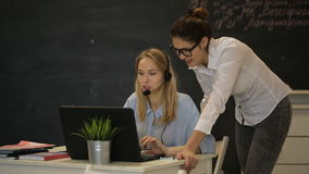 Two young businesswomen works at the computer in the office. Two young businesswomen having a meeting in the office sitting at a desk having a discussion with stock footage