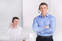 Two young call center men talking by phone. Royalty Free Stock Photos