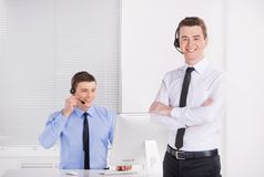 Two young call center men talking by phone. Royalty Free Stock Photography