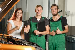 Two young car service workers, and a beautiful young girl show o royalty free stock image