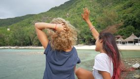 Two Young Carefree Hipster Girls Enjoing Sea View and Spreading arms. HD Slowmotion. Koh Phangan, Thailand. stock video
