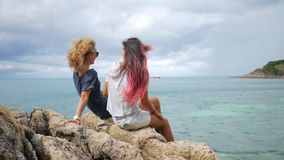 Two young carefree hipster girls enjoing sitting on rocks near sea and spreading arms. hd slow motion back view. Koh. Two Young Carefree Hipster Girls Enjoing stock video footage
