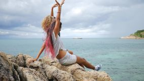 Two Young Carefree Hipster Girls Enjoing Sitting on Rocks near Sea and Spreading arms. HD Slow Motion Back View. Koh. Two Young Carefree Hipster Girls Enjoing stock footage