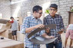 Two young carpenters discussing about furniture materials Stock Photos
