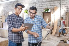 Two young carpenters discussing about furniture materials Royalty Free Stock Photography