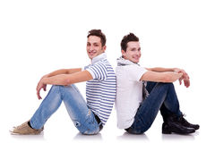 Two young casual men sitting back to back Royalty Free Stock Images