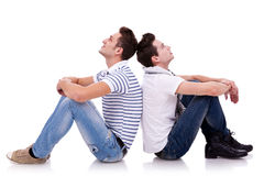 Two young casual men sitting back to back Stock Photo