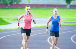 Two Young Caucasian Athletes Running Closely to Each Other. Jogging and Fitness Concepts. Two Young Caucasian Athletes Running Closely to Each Other Outdoors Stock Images