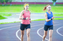 Two Young Caucasian Athletes Running Closely to Each Other Outdoors. Jogging Concepts. Two Young Caucasian Athletes Running Closely to Each Other Outdoors Royalty Free Stock Photos